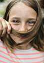 Portrait of smiling girl holding strand of hair under her nose - MGOF000276
