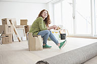 Young woman in new flat sitting on cardboard box - RBF002778