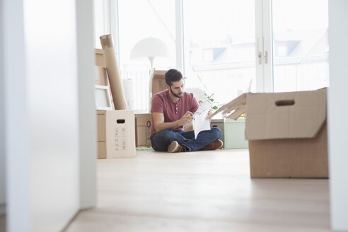 Young man in new flat with cardboard boxes holding ground plan - RBF002859