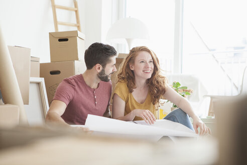 Young couple in new flat with cardboard boxes holding ground plan - RBF002779