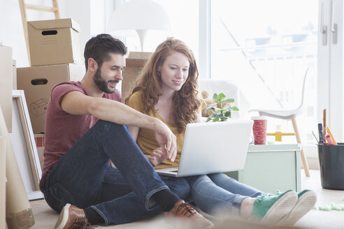 Young couple in new flat with cardboard boxes, using laptop - RBF002781