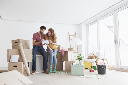 Young couple in new flat with cardboard boxes looking at ground plan - RBF002866