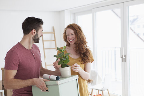 Young couple in new flat with cardboard boxes unpacking boxes - RBF002784