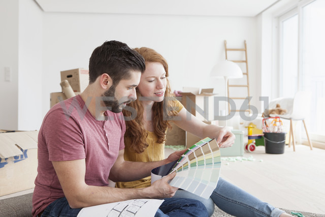 Young couple moving into new flat, choosing wall colors - RBF002786