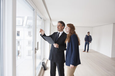 Young couple viewing flat with estate agent - RBF002794