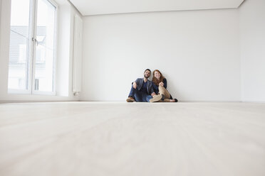 Young couple sitting on floor of their new flat - RBF002811