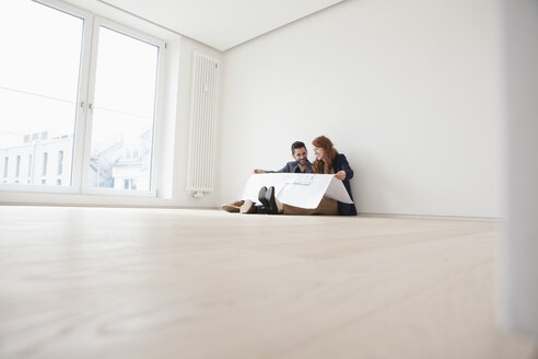 Young couple sitting on floor of their new flat, looking at ground plan - RBF002814