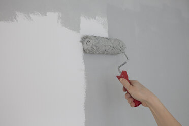 Hand of boy painting wall with paint roller - RBF002821