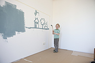 Little boy painting house and tree on wall of his new room - RBF002827