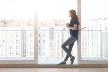 Young woman leaning at sliding door of balcony looking at distance - RBF002753