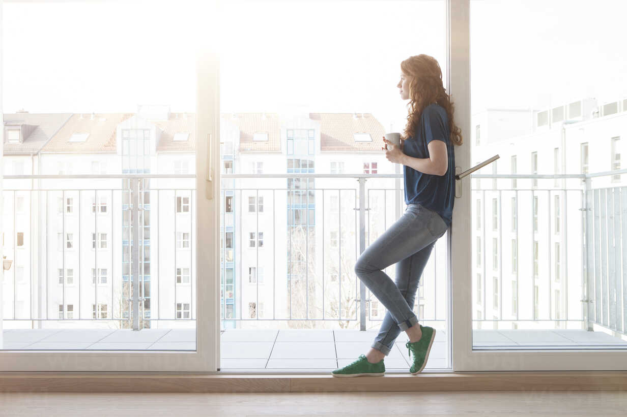 Young woman leaning at sliding door of balcony looking at distance - RBF002753 - Rainer Berg/Westend61