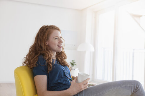 Happy young woman with cup of coffee sitting in her living room - RBF002754