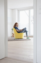 Young woman sitting on yellow armchair in her living room - RBF002832