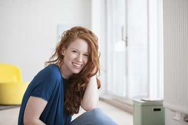 Portrait of happy young woman sitting on the floor of her living room - RBF002759