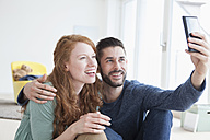 Smiling young couple taking a selfie with smartphone in the living room - RBF002838