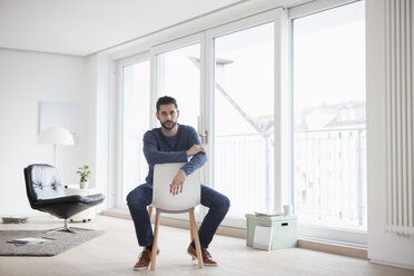 Young man sitting on chair in his living room - RBF002843