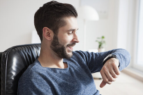 Smiling young man sitting on leather chair looking at his smartwatch - RBF002766
