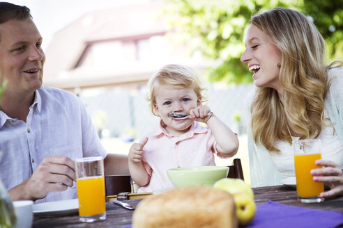 Happy family sitting at breakfast table - GDF000740