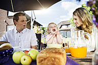 Family sitting at breakfast table in the garden - GDF000745