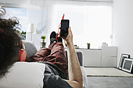 Young man lying on couch at home listening music with headphones and smartphone - PDF001081