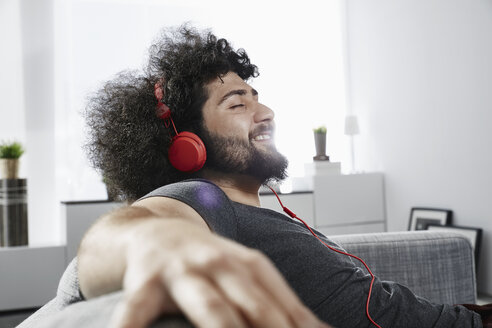 Young man sitting on couch at home listening music with headphones - PDF001075