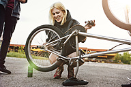 Young woman repairing BMX bicycle - GCF000121