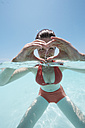 Maldives, woman shaping a heart with her hands in shallow water - STKF001290