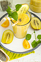 Apricot-kiwi-smoothie with chia seeds and mint in a glass with drinking straw - ODF001138