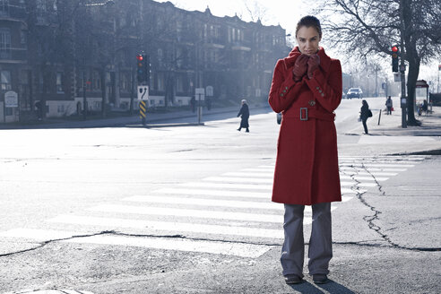 Woman wearing red coat standing at crossroad in gray city - MHCF000015