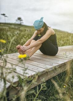 Spain, Gijon, woman doing yoga exercises - MGOF000284