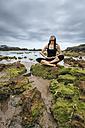 Spain, Gijon, woman doing yoga exercises - MGOF000285