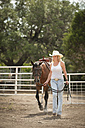 Cowgirl leading horse out of a corral - ABAF001800