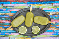 Metal tray of avocado ice lollies and slices of lime - SARF001864