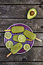 Avocado ice lollies and slices of lime on plate - SARF001869