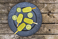 Plate of avocado ice lollies and slices of lime - SARF001870