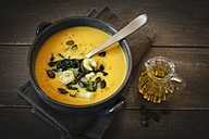 Bowl of creamed pumpkin soup with fried Chinese cabbage and pumpkin seed - EVGF001839