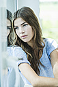 Portrait of a serious brunette young woman at the window - UUF004672