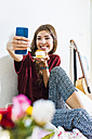 Relaxed young woman at home in bed taking selfie with piece of cake - UUF004680