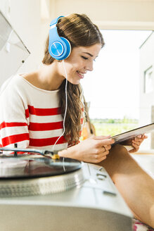 Young woman at home with headphones listening to music from record player - UUF004687