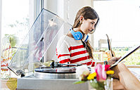 Young woman at home looking at records - UUF004688