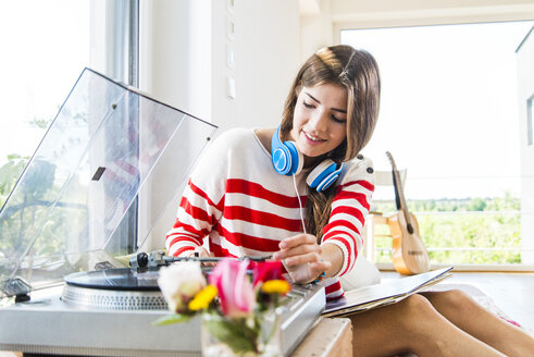 Young woman at home with record player - UUF004689