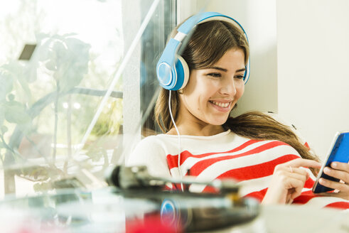 Young woman at home with headphones and smartphone - UUF004690