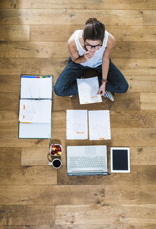 Student sitting on wooden floor surrounded by papers, laptop, digital tablet, file folder, coffee and fruit bowl - UUF004701