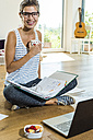 Smiling young woman sitting on wooden floor with file folder and laptop - UUF004745