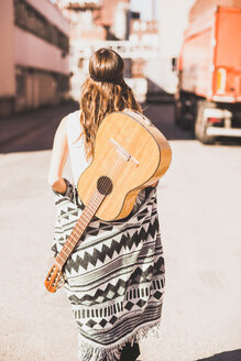 Young woman with guitar on her back walking on street - UUF004712