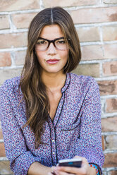 Portrait of a brunette young woman with glasses outdoors - UUF004720