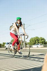 Young woman riding bicycle on pavement at the street - UUF004730