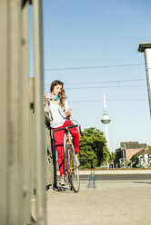 Young woman with bicycle on pavement looking at cell phone - UUF004731