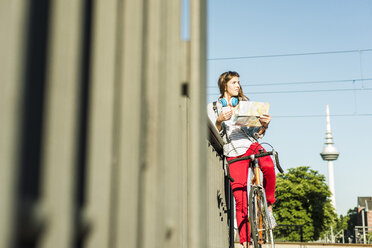 Young woman with bicycle holding map - UUF004732