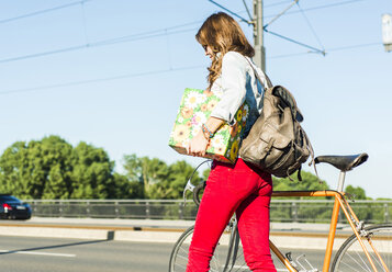 Young woman with bicycle on the street holding gift box - UUF004735